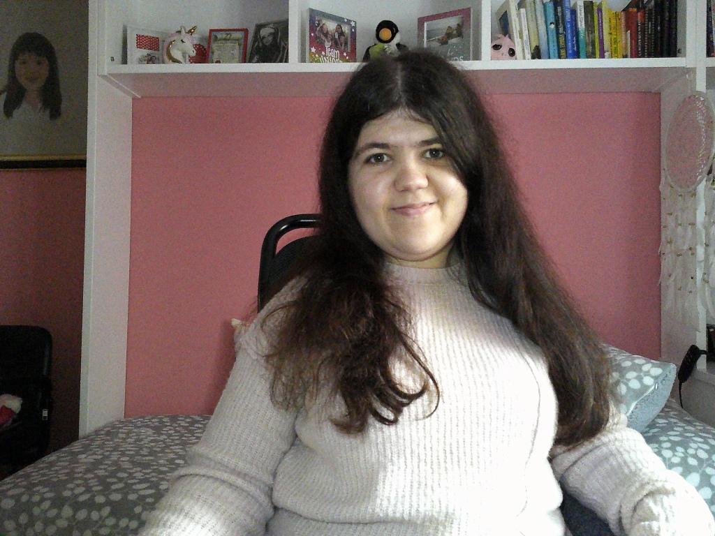 Imagen de mi en mi habitación, tengo un jersey blanco y el pelo moreno largo, sonrío