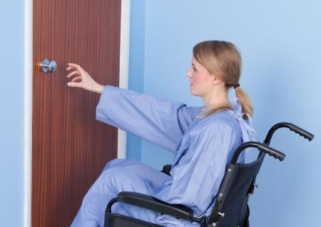 Mujer en silla de ruedas cogiendo el pomo de la puerta. Fondo de la pared y su mono es azul bebé
