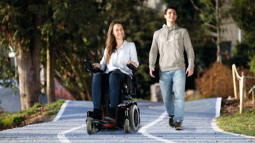 Dos personas andando por la calle, una de ellas va en silla eléctrica y la otra no.